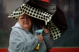 A woman braves the Nor'easter along Washington Street as it brings rain and wind to the area Tuesday, October 26, 2021, in Norwalk, Conn