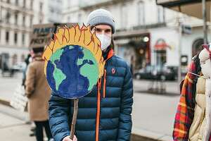 Protester holding a sign with a burning Earth at a protest against climate change.
