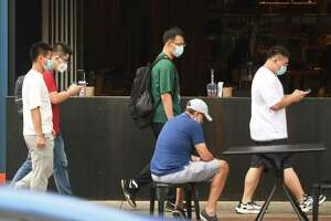 Folks wear masks while walking down Bedford Street in Stamford, Conn. Tuesday, Aug. 10, 2021.