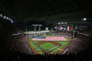 Fans and players listen to the national anthem before the start of game 1 of the World Series between the Houston Astros and the Atlanta Braves at Minute Maid Park on Tuesday, Oct. 26, 2021, in Houston.