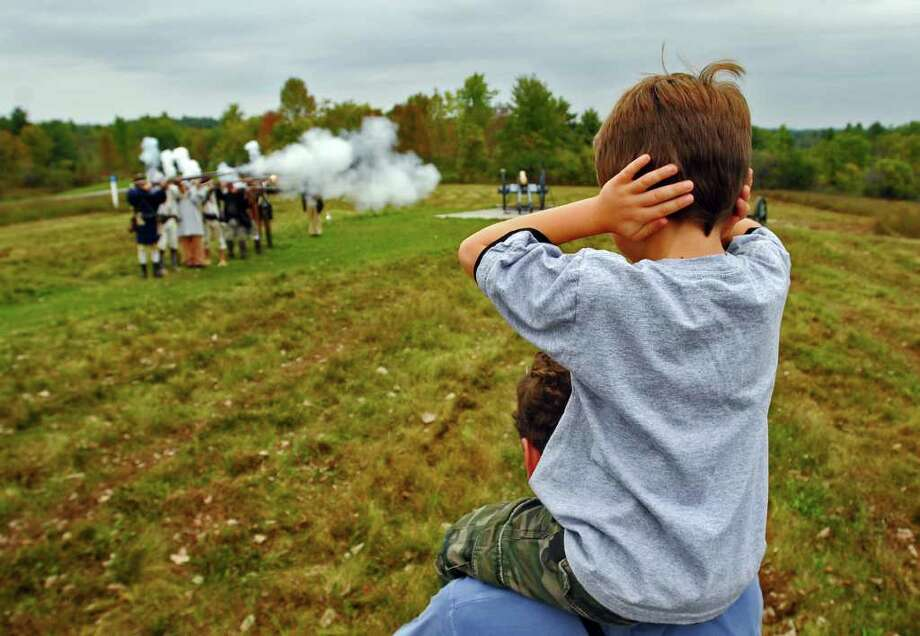 Will Marsh of Williamstown, Mass., 6, covers his ears while sitting atop his father Kevin's shoulders, as Continental Army  reenactors fire their muskets, during Sunday's 233rd anniversary of the Battles of Saratoga, at the Saratoga National Historical Park in  Stillwater.  ( Philip Kamrass / Times Union ) Photo: Philip Kamrass