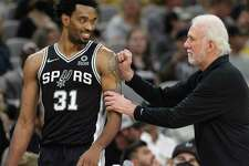 Spurs head coach Gregg Popovich (right) offers praise to Keita Bates-Diop (31) during the game against the Lakers at the AT&T Center on Tuesday, Oct. 26, 2021. Lakers defeated the Spurs, 125-121, in overtime.