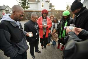 Family members of Brian Stukes stand in prayer after lighting candles at the spot on Coleman Street in Bridgeport, Conn. where Stukes died after being shot by Bridgeport police on April 1, 2013.