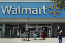 People wearing protective masks walk from a Walmart store on May 18, 2021 in Hallandale Beach, Florida.
