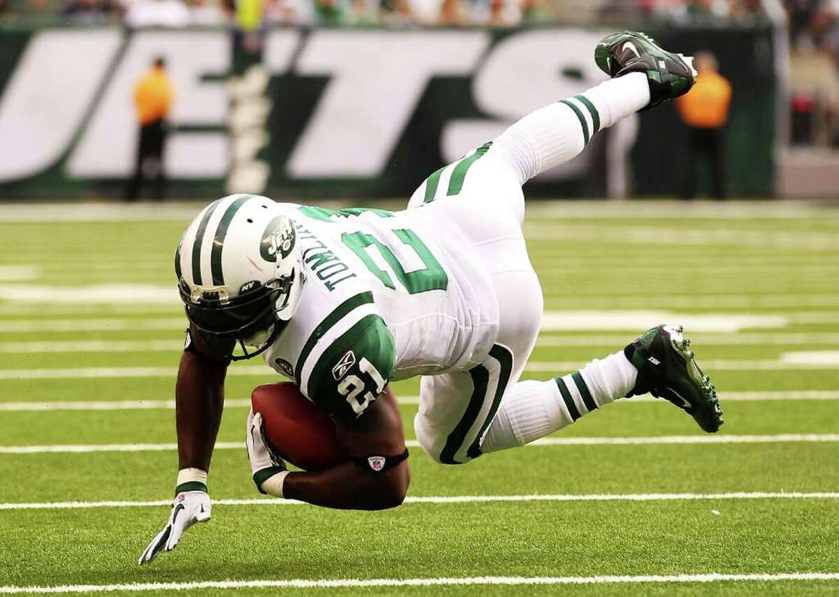 EAST RUTHERFORD, NJ - SEPTEMBER 19: LaDainian Tomlinson #21 of the New York Jets is tripped up by Devin McCourty #32 of the New England Patriots on September 19, 2010 at the New Meadowlands Stadium in East Rutherford, New Jersey. (Photo by Al Bello/Getty Images) *** Local Caption *** LaDainian Tomlinson