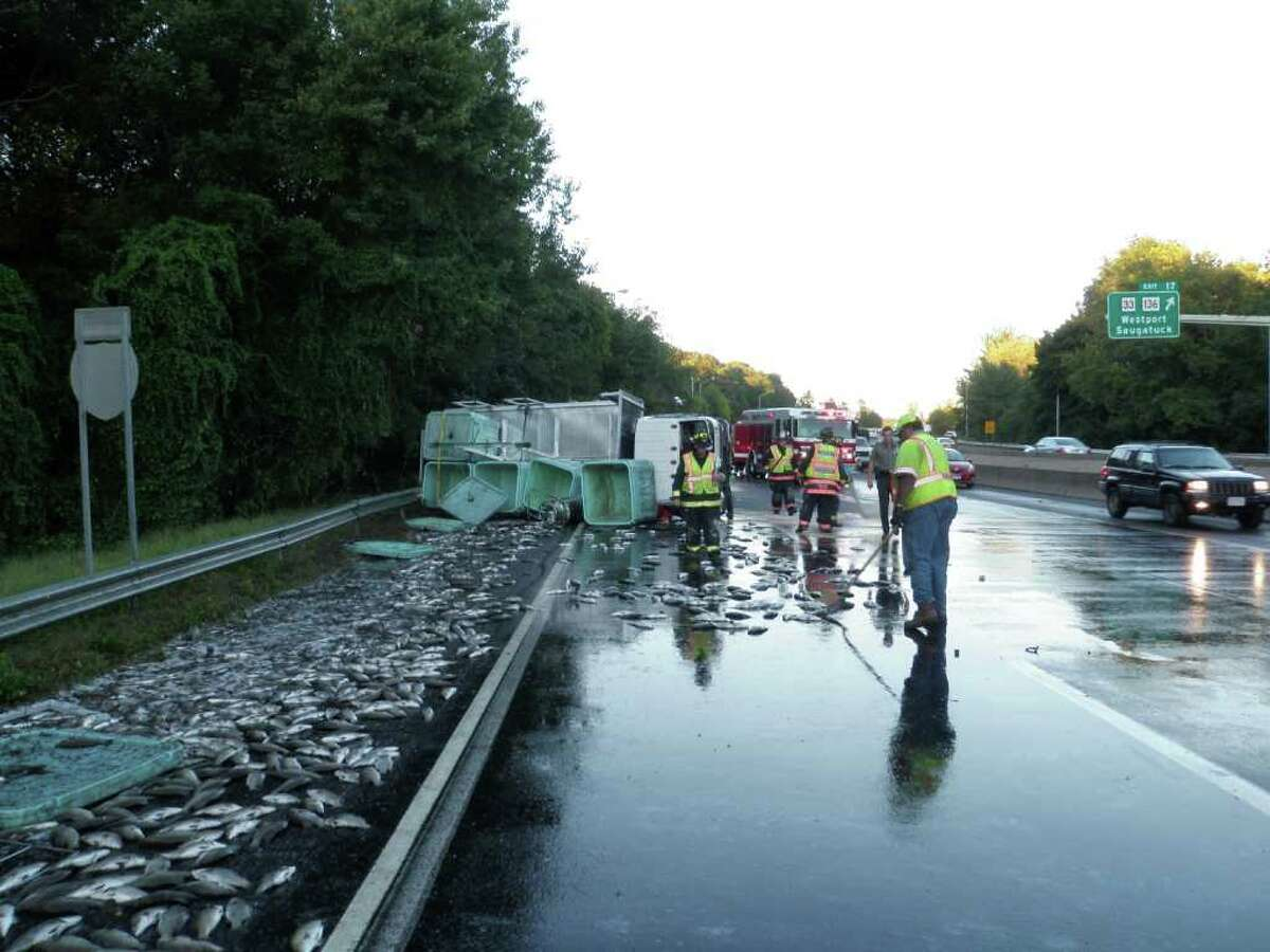 Emergency crews clean 2,500 pounds of live fish from Interstate 95 on Monday, Sept. 20, 2010, following a rollover that closed two lanes of traffic on the southbound side for nearly four hours. The driver was uninjured in the accident, but the load of fish was condemned by the Connecticut Department of Consumer Protection.