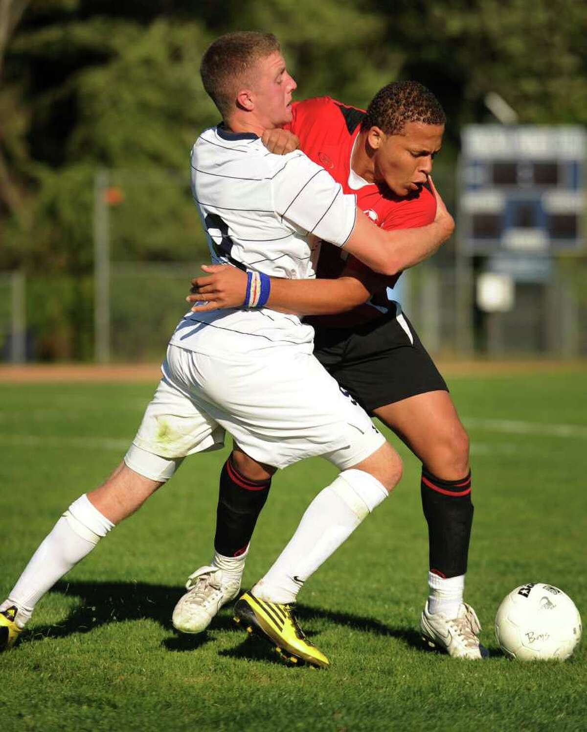 Staples' Brendan Lesch, left, and Bridgeport Central's Jenilo Soares, grapple as they look to play the ball during their FCIAC boys soccer matchup at Staples High School in Westport on Monday, September 20, 2010.