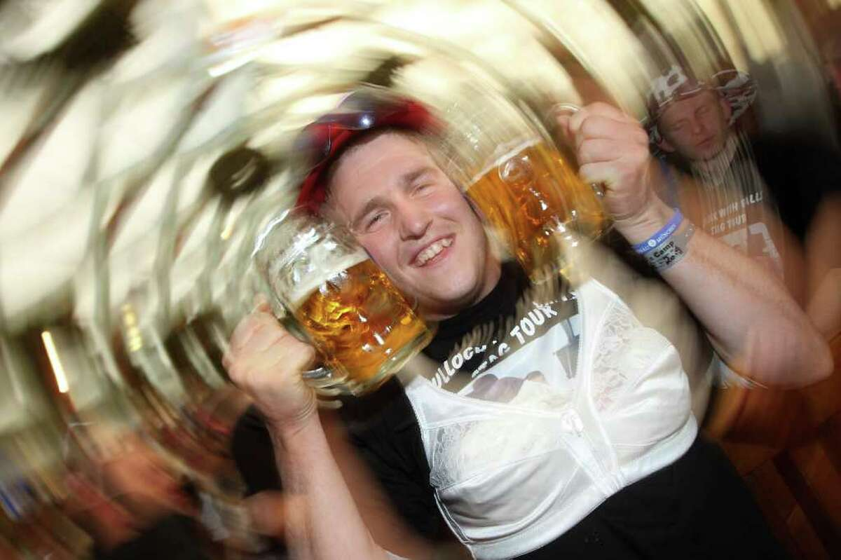 MUNICH, GERMANY - SEPTEMBER 20: A man wearing a bra holds two beer mugs next to his face at the Hofbraeu tent during day 3 of the Oktoberfest at Theresienwiese on September 20, 2010 in Munich, Germany. 2010 marks the 200th anniversary of Oktoberfest.The Oktoberfest tradition started in 1810 to celebrate the October 12th marriage of Bavarian Crown Prince Ludwig to the Saxon-Hildburghausen Princess Therese. The citizens of Munich were invited to join in the festivities which were held over five days on the fields in front of the city gates. The main event of the original Oktoberfest was a horse race. The world's biggest beer festival will last this year from September 18 to October 4. (Photo by Miguel Villagran/Getty Images)