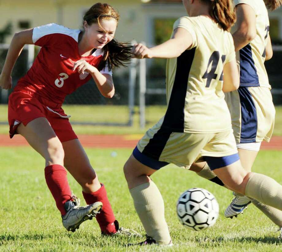 High school soccer - Mechanicville High's  Danelle Haner, left, takes a shot on goal against Cohoes High defenders during the Red Raiders' 5-0 girls' soccer victory on Monday at Cohoes.  (Luanne Ferris / Times Union) Photo: Luanne M. Ferris