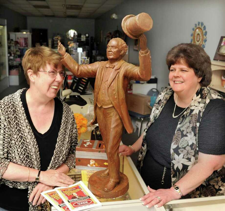 Patricia Rist, left, president of the Bethel Historical Society, brought a miniature statue of P.T. Barnum to Lorraine Schrameck at Silver Touch in the Dolan Plaza in Bethel. The minature version of a bigger statue of Barnum has made 13 other stops to stores and banks around town since June 21. This weekend is  P.T. Barnum's 200th birthday celebration in Bethel. Photo taken Tuesday, Sept. 21 , 2010. Photo: Carol Kaliff / The News-Times