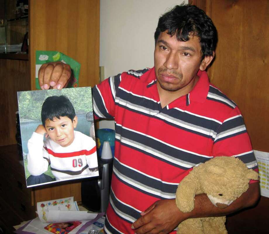 Carlos Zhunio holds up a photo and favorite toy of his 4-year-old son, Eric, who died from injuries after a pick-up truck hit him in July. Photo: File Photo / The News-Times File Photo
