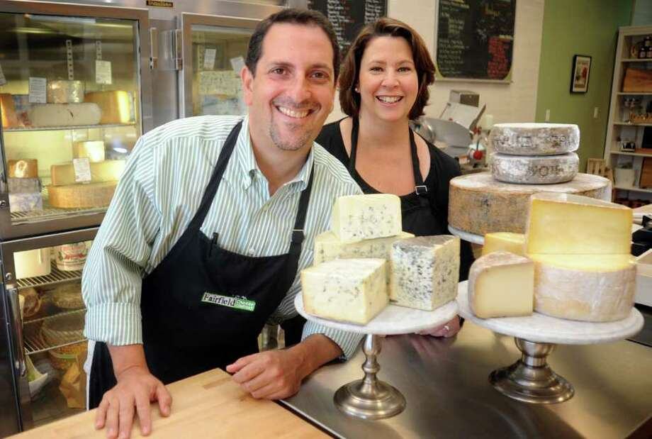Fairfield Cheese Company owners Christopher Palumbo and Laura Downey stand behind the counter with some of their artisan cheeses.  The shop at 2090 Post Road in Fairfield offers 35-40 different varieties of cheese along with other gourmet items. Photo: Autumn Driscoll / Connecticut Post