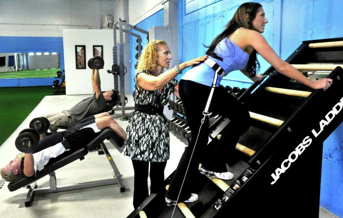 Platium Fitness owner Anna Lamorte, center, instructs her daughter Elena Lamorte, 28, of Danbury, on the Jacobs Ladder equipment, during a workout session at the center in Danbury, Tuesday, Sept. 21, 2010.