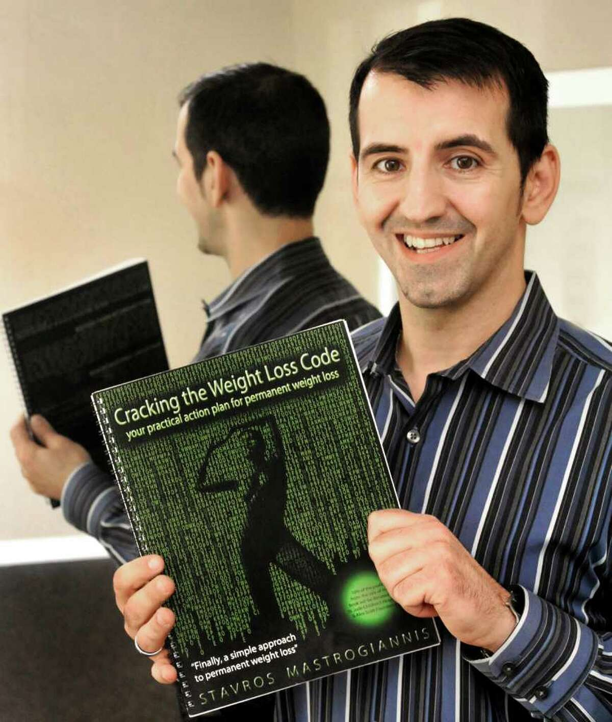 Stavros Mastrogiannis holds his new book, Cracking the Weight Loss Code, at Olympus Personal Training & Weight Management in Danbury, Tuesday, Sept. 21, 2010.