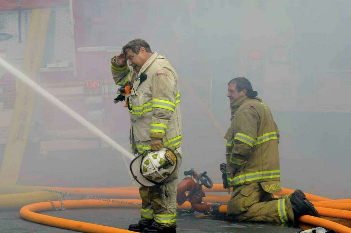 Firefighters work at the scene of a fire at 3237 Seventh Ave. in Troy Wednesday morning. (Michael P. Farrell / Times Union)