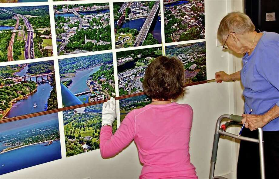 "Ellen Naftalin (left) and Molly Donovan (right) hang photographs for the Westport Historical Society's new ""Zoom in on Westport"" exhibit. An opening reception for the exhibit will be held at the Society on Sunday, Oct. 3, 2010. Photo: Contributed Photo / Westport News contributed"