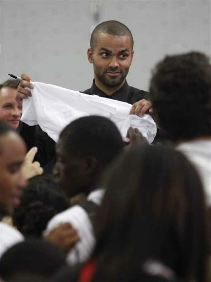 Spurs guard Tony Parker  signs a shirt as he inaugurates a gymnasium bearing his name in Charenton, outside Paris, on Wednesday.