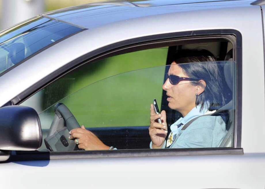 A woman speaks into a mobile device while driving on East Putnam Avenue in the Riverside section of Greenwich, Tuesday evening, Sept. 21, 2010. Photo: Bob Luckey / Greenwich Time