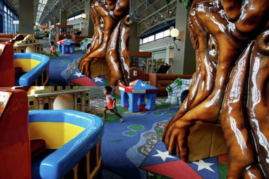 Two-year-old Aarav Singhal plays in the children's play area at Rivercenter mall. Owners of the downtown mall have made changes in some areas but are holding off on others until the economy improves.