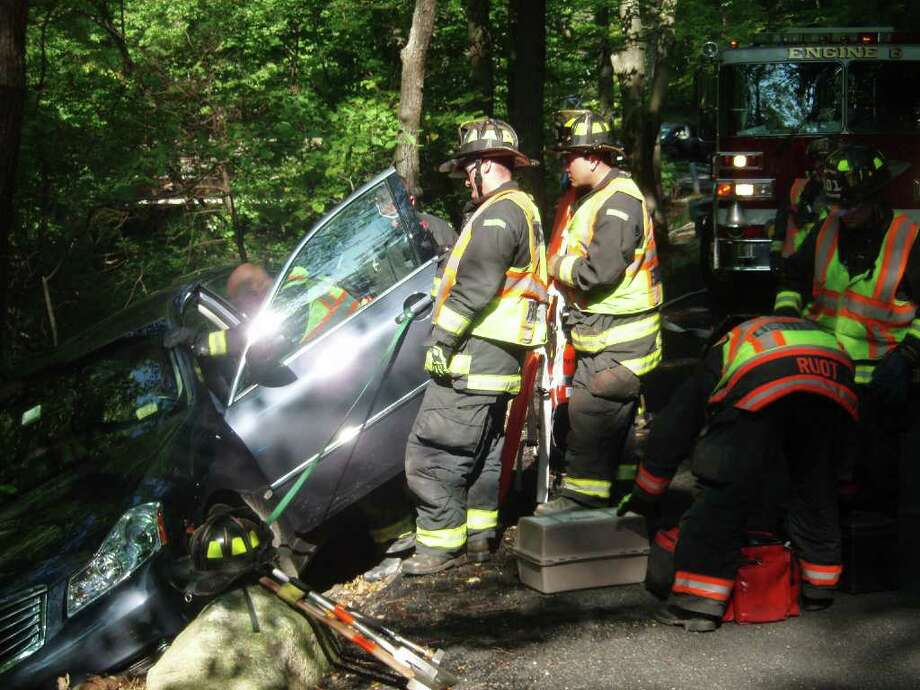 Westport firefighters rescue a driver from a vehicle that slid partially down the embankment of the Saugatuck River on Ford Road on Thursday, Sept. 23, 2010 around 3 p.m. Photo: Contributed Photo / Westport News