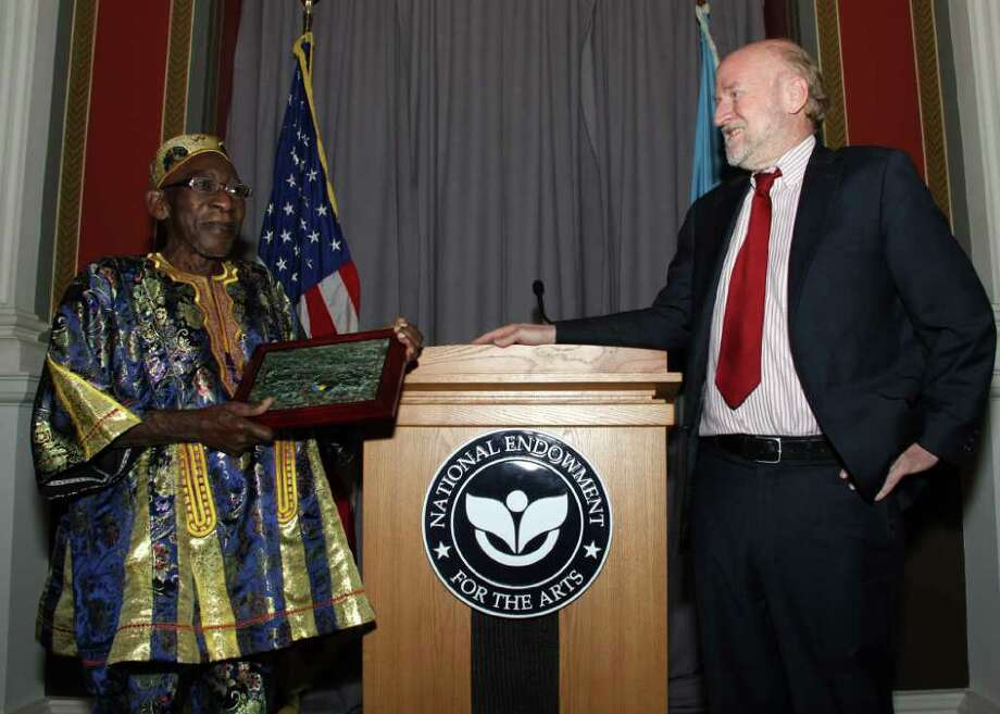 Yacub Addy, a Ghanaian drum master from Latham, accepts his NEA National Heritage Fellowship award from National Endowment for the Arts Chairman Rocco Landesman at an awards ceremony at the Library of Congress on Sept. 22. Rocco Landesman said, ?A master of the traditional Ga music, Yacub Addy is a generous mentor of aspiring drummers as well as a collaborator with jazz and popular musicians, who has created new works that speak to issues of social and cultural relevance today.? (Michael G. Stewart)