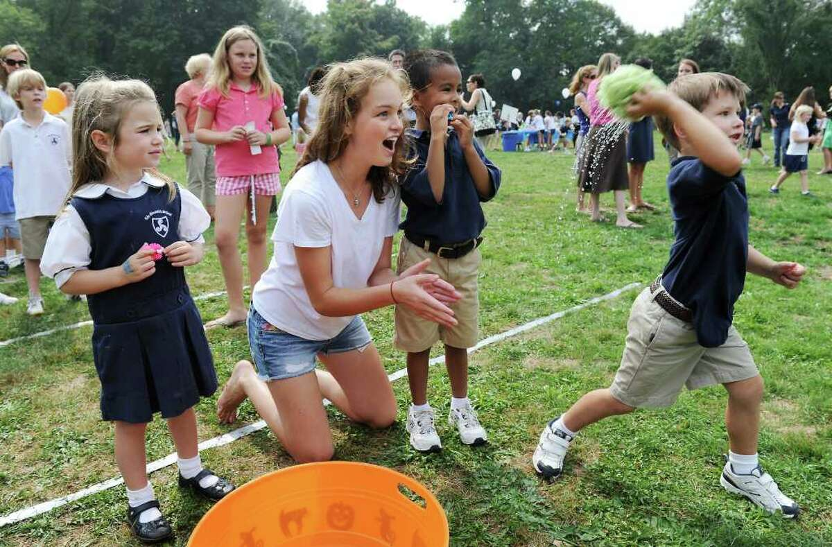 Eighth grader Natalie Gustin coaches kindergarden student Lochlan Laitala, 5 of Greenwich, in the sponge throw game at the 2nd Annual Stanwich Family Festival at the Stamford campus in Stamford, Conn. on Friday September 24, 2010