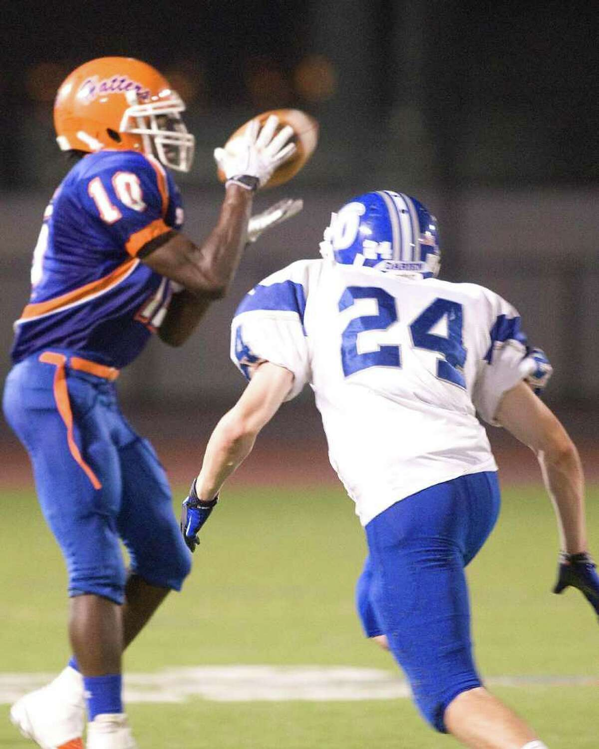 Danbury's Daryle-Michael Dennis (10) catches a pass before being stopped by Darien's Peter McDonough during their FCIAC game Friday night, Sept. 24, 2010, at Danbury High School.