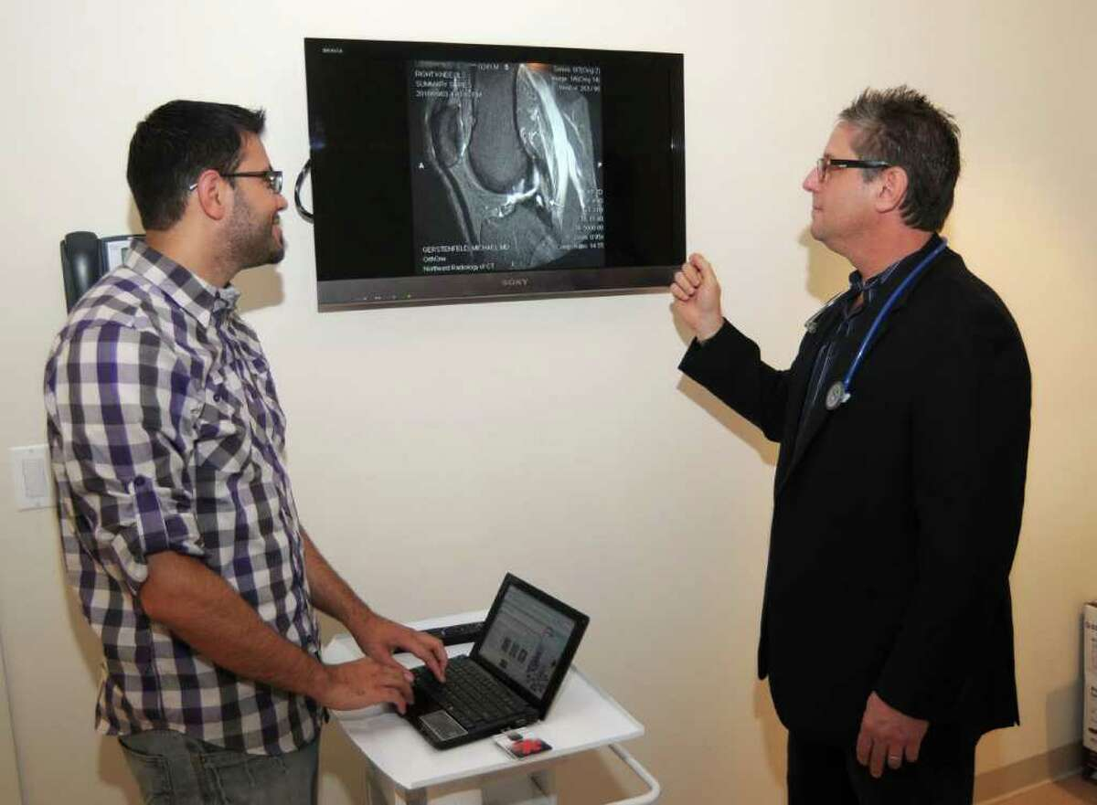Dr. Mike Gerstenfeld,right, of the imedcenter.com of Danbury,and chief technology officer, Matt Meier, right, look at an MRI of a patients knee, on Friday, September 24, 2010.