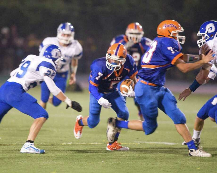 Danbury's Anthony Nejame (7) picks up a first down after catching a pass from quarterback Nick Hamed.  Teammate William Jack provides a block while Darien's Cody Dizeo (29) moves in to make the tackle during an FCIAC game Friday, Sept. 24, 2010, at Danbury High School. Photo: Barry Horn / The News-Times Freelance