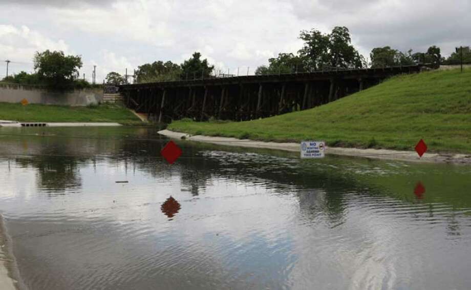 Signs warn boaters about a restricted area near the Eagleland section of the San Antonio River. Cables keep boaters from going farther, but the city is seeking an alternative.