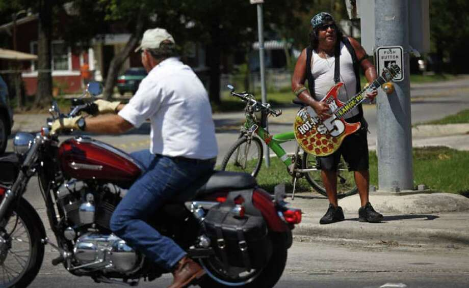 Ronnie Epstein entertains drivers as he silently jams to music on his headset outside Little Caesars Pizza at the corner of Walnut Avenue and West San Antonio Street last week in New Braunfels.