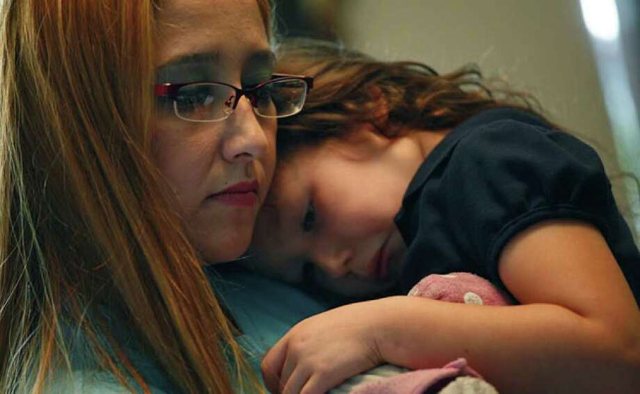Housing authority client Melissa Ann Rodriguez holds her daughter Korissa Perez, 4, while she helps her sons with their homework.