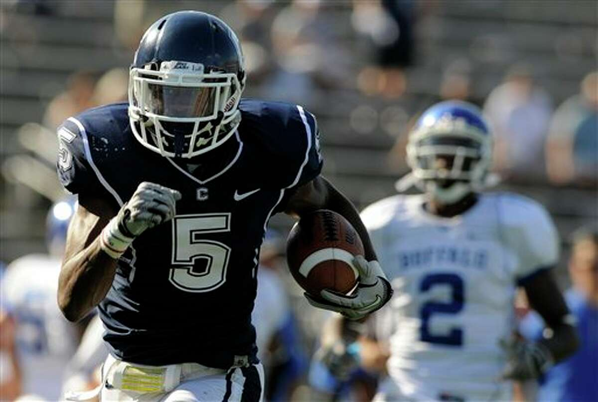 Connecticut's  Blidi Wreh-Wilson returns an interception 46 yards for a touchdown as Buffalo's Marcus Rivers looks on during the second half of Connecticut's 45-21 victory in an NCAA football game in East Hartford, Conn., on Saturday, Sept. 25, 2010.