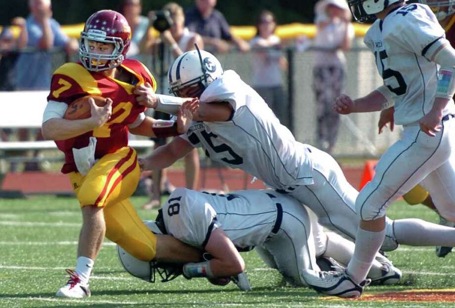 St. Joseph's Joe Della Vecchia tries to fend off a tackle by Wilton's Rob Keers, bottom, and Mark Peidmont during the second half of their football game Saturday September 25, 2010 at St. Joseph's Dalling Field in Trumbull. Photo: Autumn Driscoll / Connecticut Post