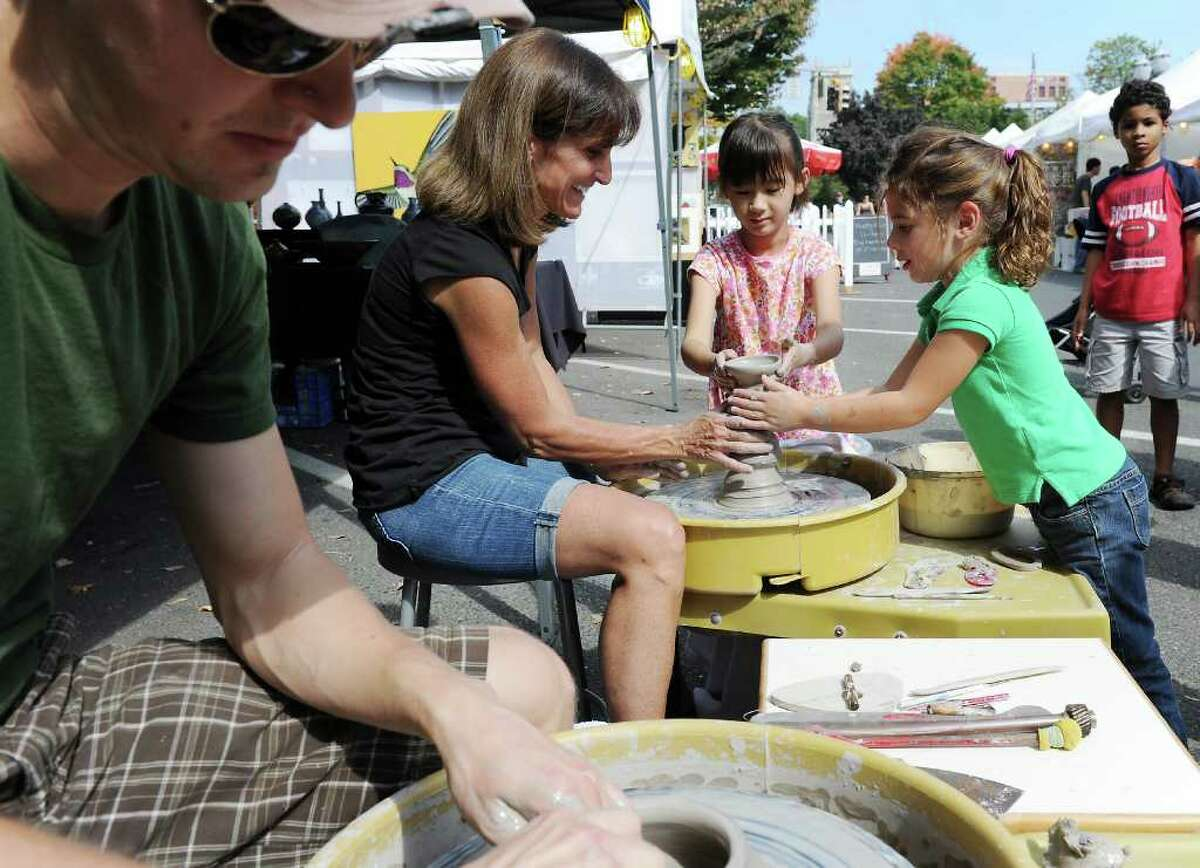 Katya Avvakumova, 6 of Stamford, and Isabella Siciliano, 3 of Stamford, work on a pottery wheel with Patty Storms, of Lakeside Pottery, at Arts & Crafts on Bedford presented by the Stamford Downtown Special Services District in Stamford, Conn. on Saturday September 25, 2010