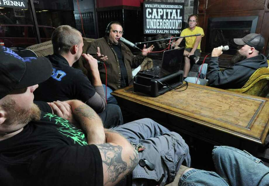 "Music promoter Ralph Renna, center, interviews the band ""Apathy Arising"" on his ""Capital Underground with Ralph Renna"" Internet radio show at Savannah's in Albany, NY on September 15, 2010.  Band members are Bonesteel, singer, far left, Liam Malone, Drums, second from left, and Ryan Butt, guita, far right. Bass player Jonathan Denaker is on couch but not in photo. Person in background was not in band. He was just listening to the interview. (Lori Van Buren / Times Union) Photo: Lori Van Buren"