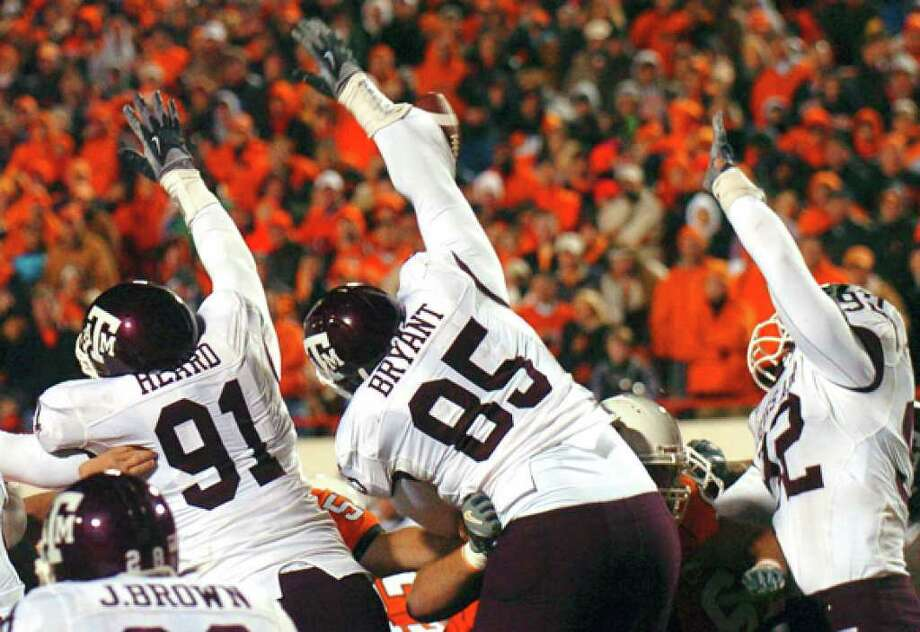 Texas A&M's Red Bryant (center) deflects Oklahoma State's overtime extra-point kick to win a 34-33 decision on Oct. 21, 2006.