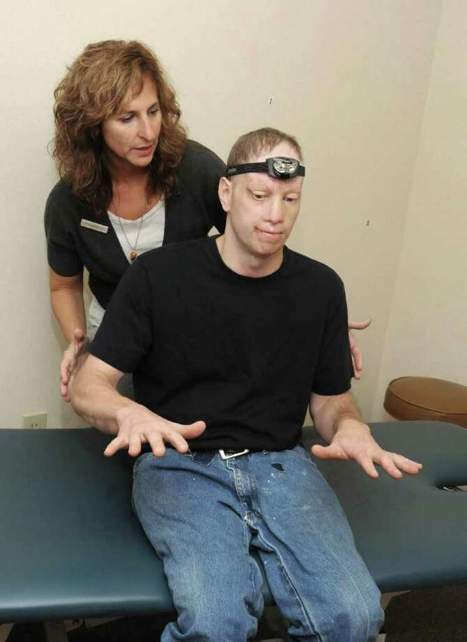 Dr. Lisa Dransfield, director of The Balance and Vestibular Center at Associated Neurologists in Danbury, works with, Mark Carminucci, of Newtown, in the office on Friday Sept. 24, 2010. The center helps people suffering from dizziness and vertigo. Photo: Lisa Weir / The News-Times Freelance