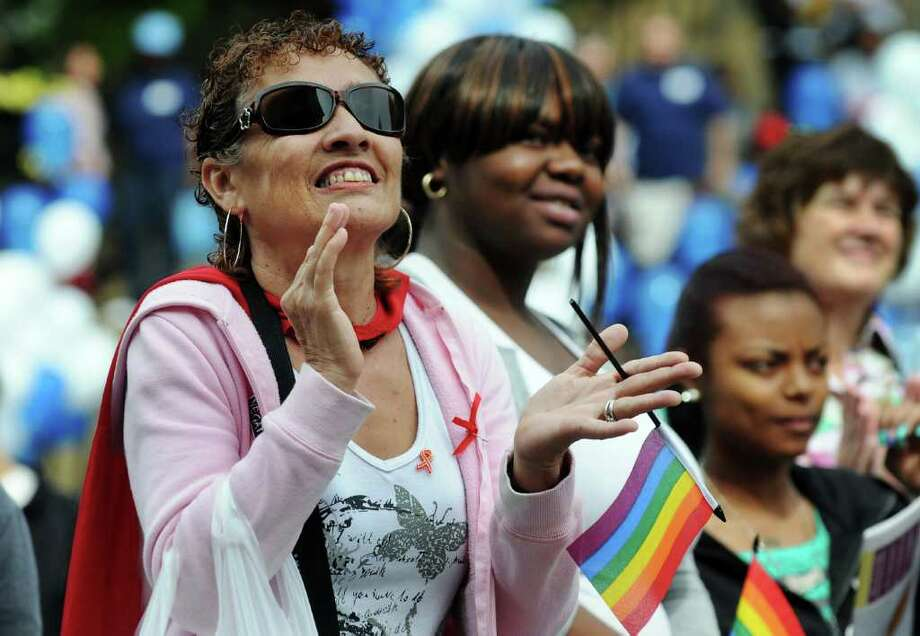 "Maria Aponte, of Albany, left, joins in singing  ""We Shall Overcome"" during the 14th annual AIDSWalk and 5K Run on Sunday in Albany's Washington Park. (Cindy Schultz / Times Union) Photo: Cindy Schultz"