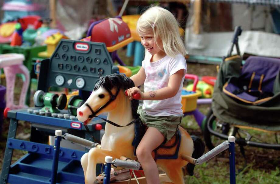 Four-year-old Samantha Edwards, of Westport, tries out a toy pony for sale at Emmanuel Episcopal Church's 104th annual Country Fair Saturday September 25, 2010 in Weston. Photo: Autumn Driscoll / Connecticut Post