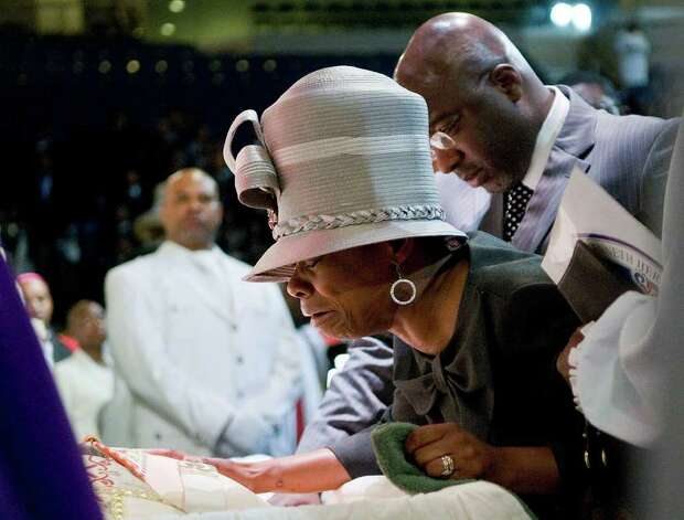 Kenya Moales-Byrd pays her last respects at the casket of her father as thousands of mourners gather for a Celebration of Life Homegoing Service for Bishop Kenneth H. Moales, Sr. on Monday September 27, 2010 at the Arena at Harbor Yard in Bridgeport, CT. Moales was the founding pastor of the Cathedral of the Holy Spirit, and was the Presiding Prelate of the Pentecostal Church of Jesus Christ. As bishop, he presided over ten states as well as the Kunjalo Dioese of Cape Town, South Africa. Photo: Shelley Cryan / Shelley Cryan freelance; Connecticut Post Freelance