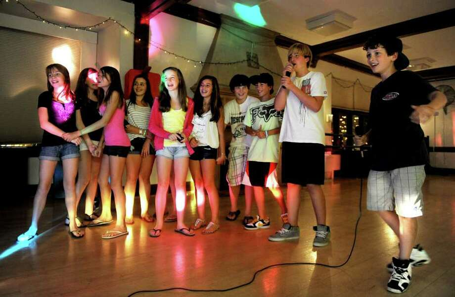 """From right, Dylan Drefuss and John Fincher sing karaoke to """"Ain't No Mountain High Enough"""" during the first Youth Fun Night of the school year at the Westport Weston Family YMCA on Saturday, September 25, 2010. Photo: Lindsay Niegelberg / Connecticut Post"""