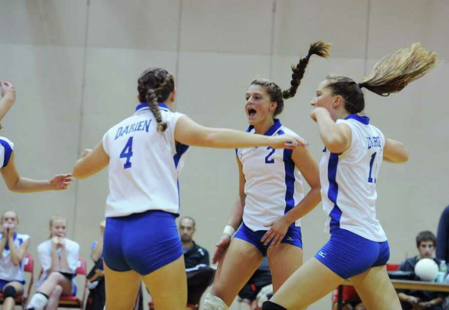 Darien's Mackenzie Begley, Emma Getsinger and Katie Stueber celebrate a point as Greenwich High hosts Darien High in a girls volleyball game Monday, September 27, 2010. Darien won 3-1. Photo: Keelin Daly / Stamford Advocate