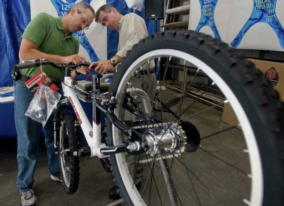 Dominic Debellis of Mahopac, N.Y., an associate director of medical writing, along with Gene Hickey of Danbury, a senior scientist, secure the brake levers on a Schwinn at Boehriger-Ingelheim. Wednesday, Sept. 22, 2010 Photo: Scott Mullin / The News-Times Freelance