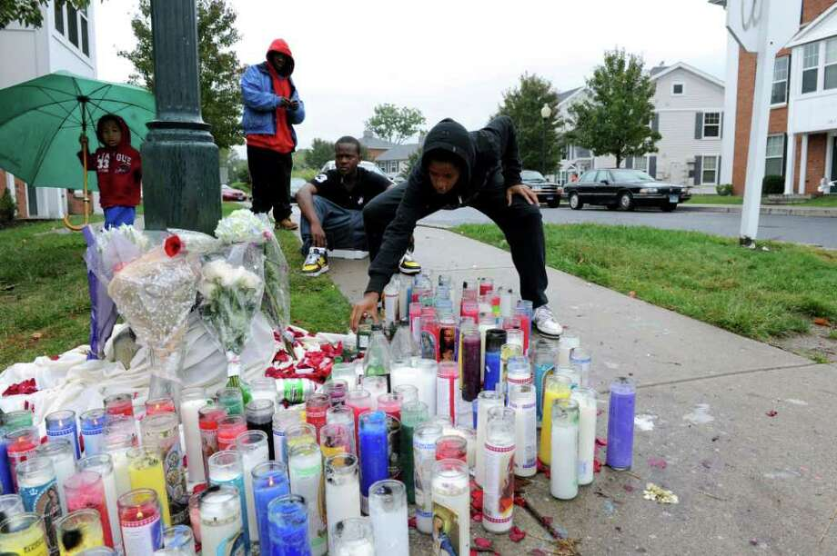 Maki Newton, 2, left, Rece Palmer, Tyshawn Malachi, seated, and Shanita Newton spend time remembering shooting victim Donta Wilks on Southwood Drive where a shrine is set up in his memory Tuesday, September 28, 2010. Newton and Malachi are Wilks' cousins. Photo: Keelin Daly / Stamford Advocate