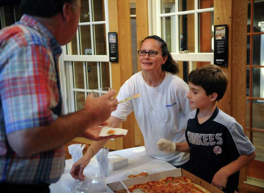 """Nancy Ugrinaj, center, and her son, Kaltrin, 9, right, serve pizza from their Byram pizzeria, Fuzari's, during the """"Taste of Byram"""" event organized by the Greenwich Chamber of Commerce at Interstate Lumber, Byram, Tuesday night, Sept. 28, 2010. Photo: Bob Luckey / Greenwich Time"""