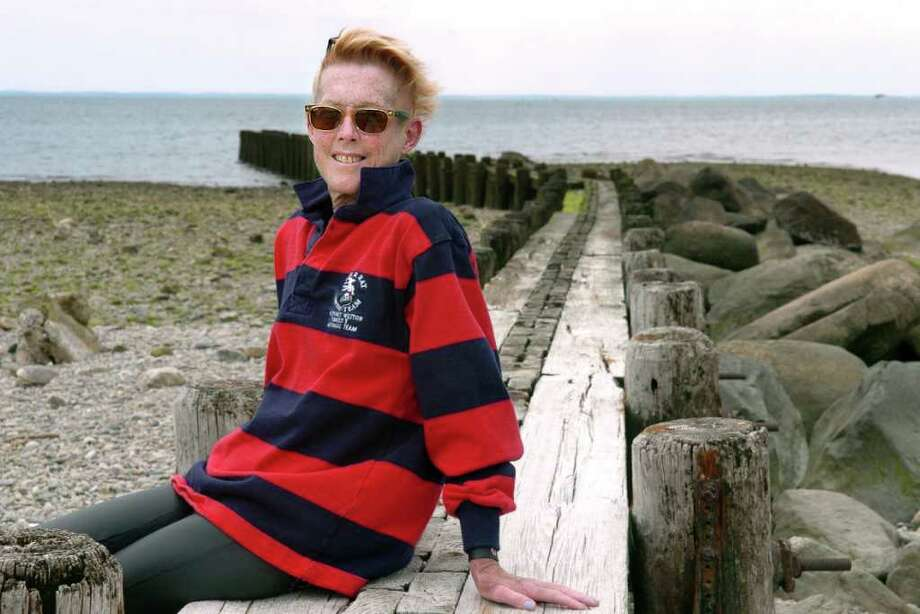 Maura Marden, of Westport, sits on the pier Tuesday June 22, 2010 at Burying Hill Beach in Westport.  Marden, a breast cancer survivor, will participate in Swim Across the Sound in August to raise money for cancer research. Photo: Autumn Driscoll, ST / Connecticut Post