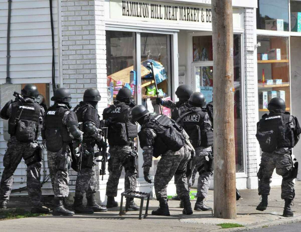 Schenectady police smash through the store window of the Hamilton Hill Meat Market & Beverage on Albany Street Wednesday, Sept. 29, 2010. (John Carl D'Annibale / Times Union)