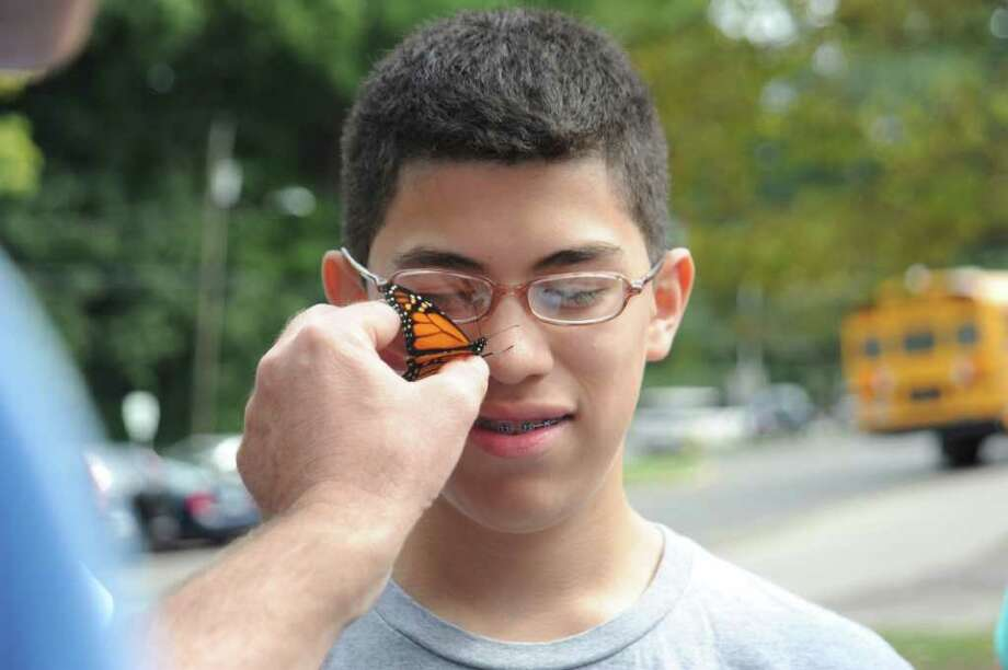 Greenwich High School biology teacher Parker Gambino holds a monarch butterfly on student Jonathan Flores's, 14, nose, before it flies away, on Wednesday, Sept. 29, 2010. Photo: Helen Neafsey / Greenwich Time