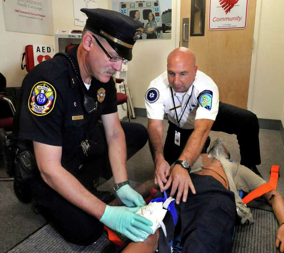 Bethel Police Capt. Robert Cedergren is instructed by Matthew Cassavechia, director of Emergency Medical Services at Danbury Hospital, on the application of CAT tourniquets to control bleeding, Thursday, Sept. 30, 2010. Cedergren will instruct area police officers on the technique. Photo: Michael Duffy / The News-Times